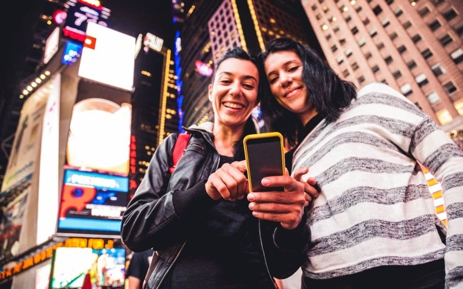 Two women use phone with ads in the background