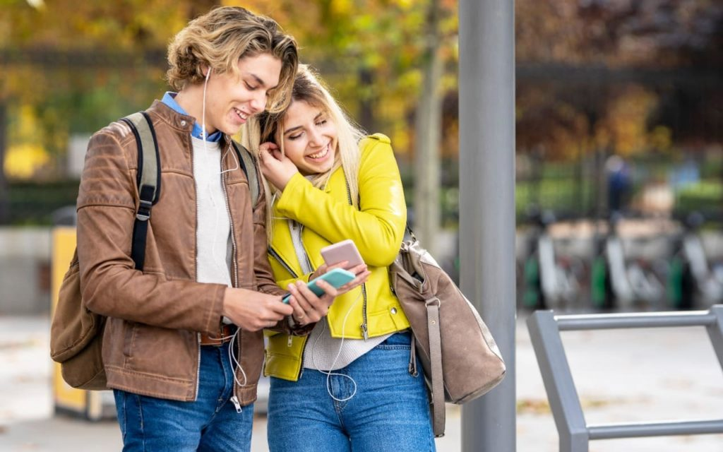 happy young man and woman couple using smartphone and listening to music in the city