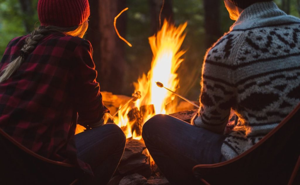 Couple enjoy story by the fire. The Art of storytelling