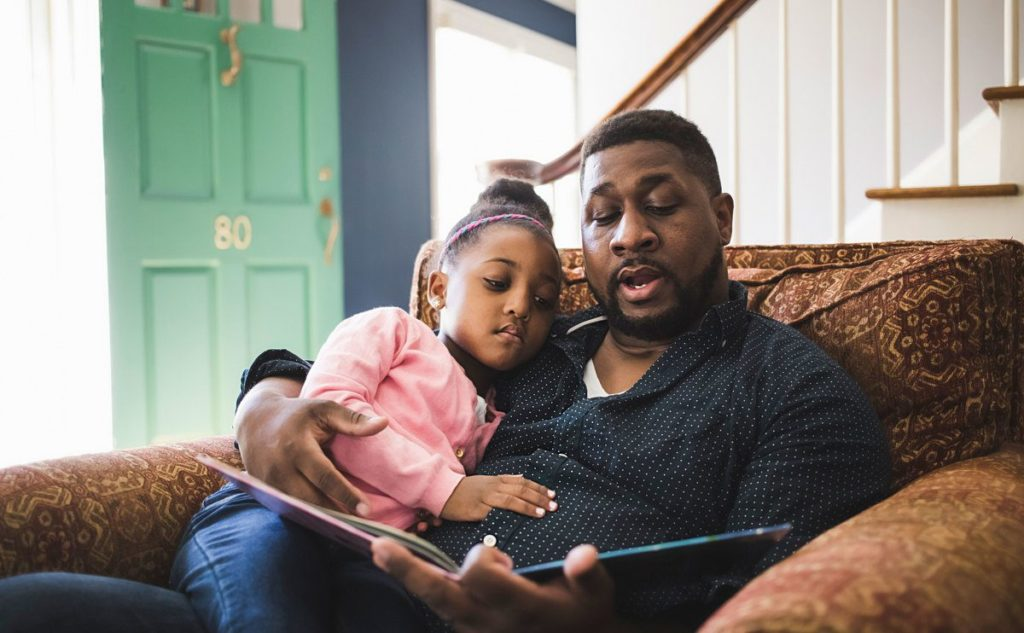 Father reading a story to his daughter. The art of storytelling